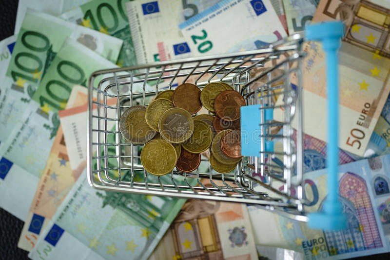 Евро чеканит в мини магазинной тележкае и куче банкноты евро на ба стоковое фото rf