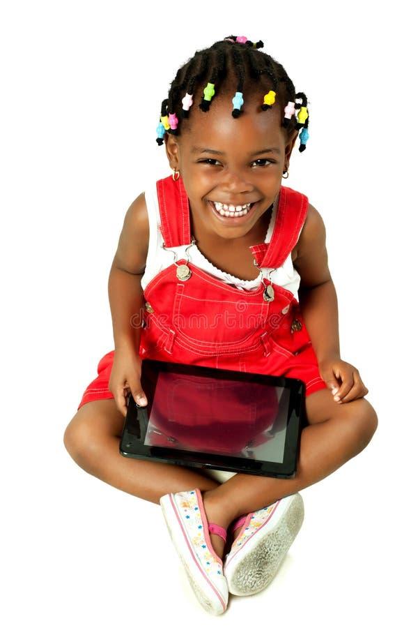 девушка афроамериканца меньшяя таблетка ПК используя стоковое изображение