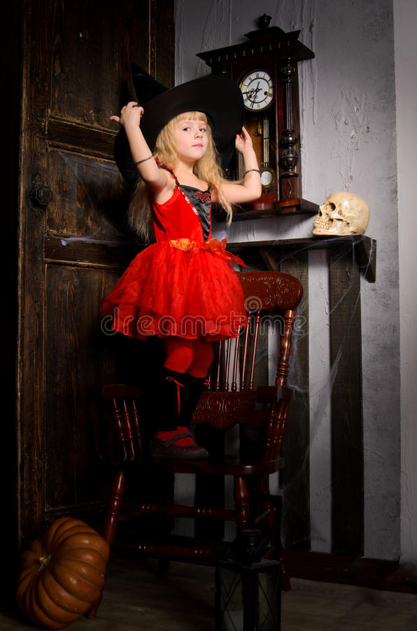 девушка ведьмы хеллоуина в красных платье и черной шляпе стоковое изображение rf