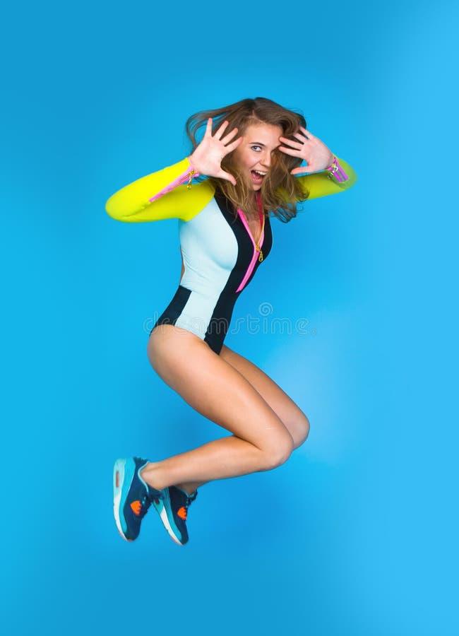 девушка предпосылки скача над детенышами студии всхода белыми стоковое фото