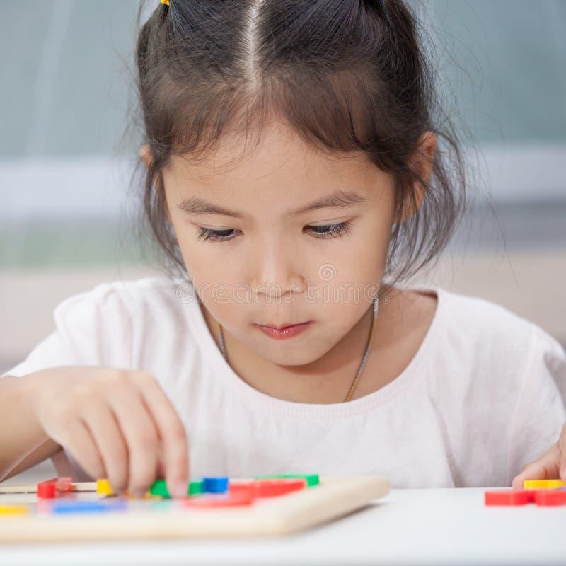 девушка ребенка имея потеху для того чтобы сыграть и выучить магнитные алфавиты стоковое изображение