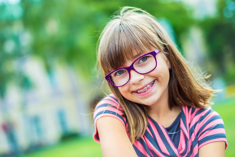 девушка teen Pre предназначенный для подростков Девушка с стеклами Девушка с расчалками зубов Расчалки и стекла зубов молодой мил стоковая фотография rf