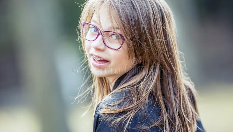 девушка teen Pre предназначенный для подростков Девушка с стеклами Девушка с расчалками зубов Расчалки и стекла зубов молодой мил стоковое изображение rf