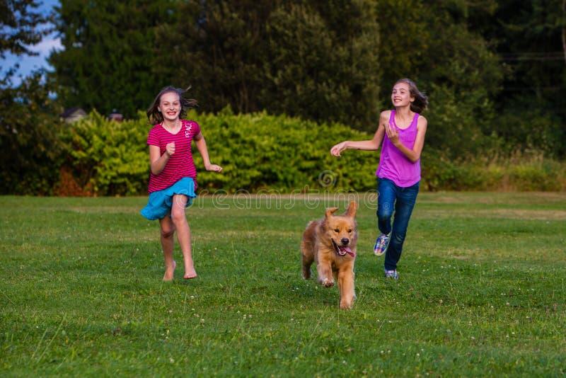 2 девушки бежать с собакой стоковая фотография