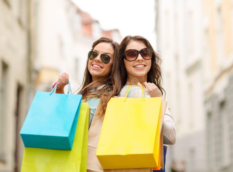 2 девушки в солнечных очках с хозяйственными сумками в ctiy стоковые изображения rf