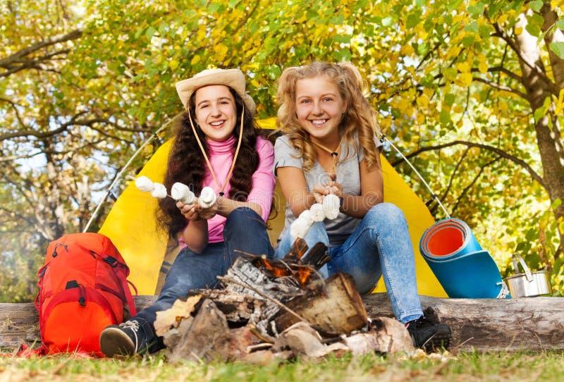 2 девушки жаря в духовке smores приближают к камину стоковое фото rf