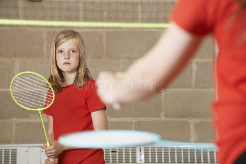 2 девушки играя бадминтон в спортзале школы стоковые фото