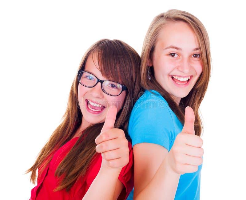 девушки показывая большие пальцы руки вверх стоковое фото