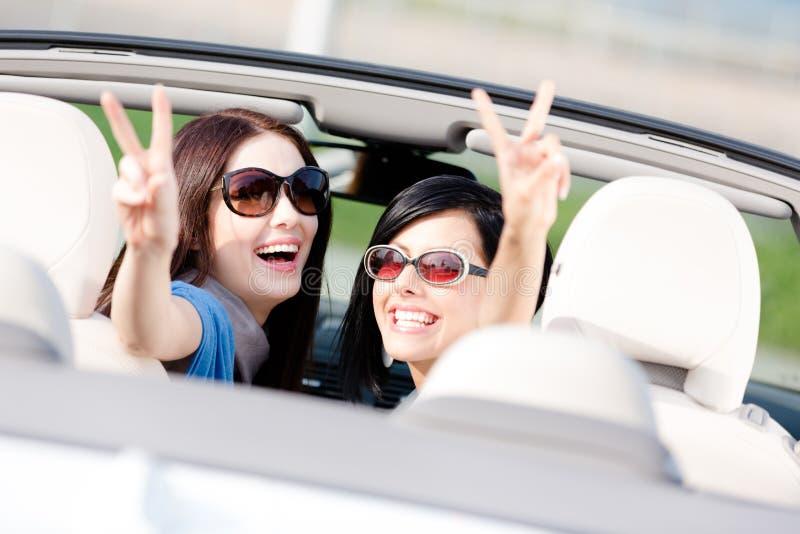 2 девушки сидя в автомобиле и показывать знак победы стоковое изображение