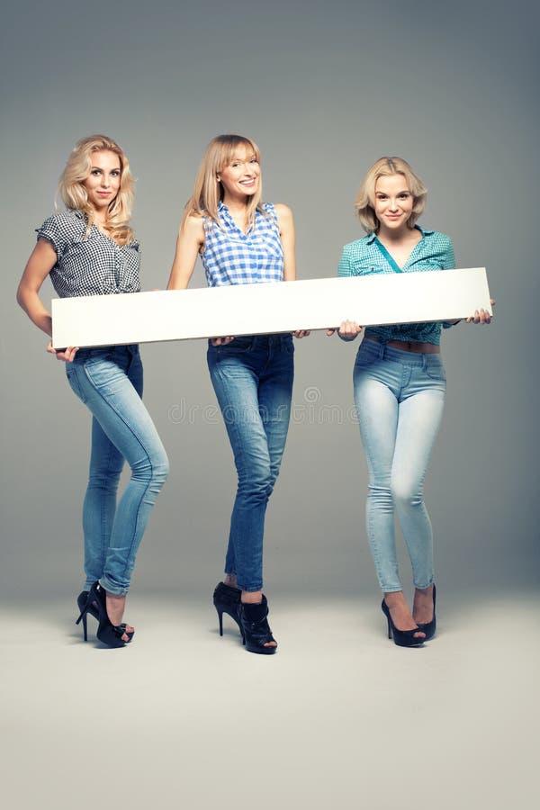 3 девушки с пустой доской стоковые изображения