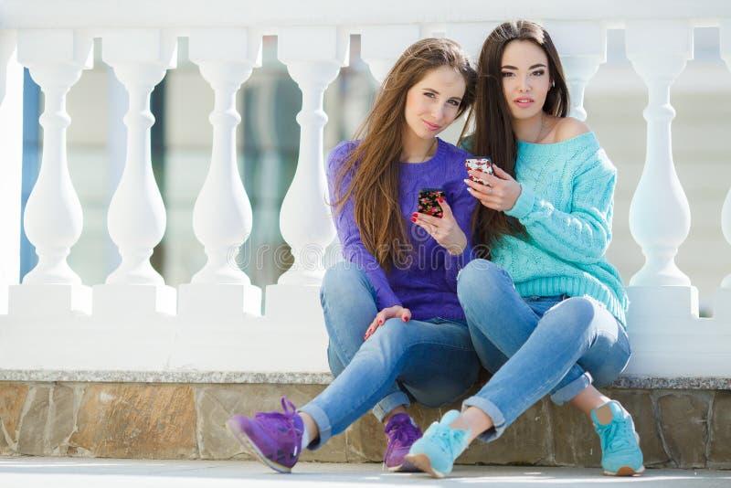 2 девушки слушая к музыке на их smartphones стоковые изображения rf