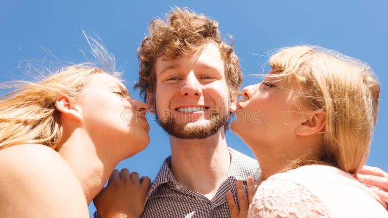 2 девушки целуя одного мальчика имея потеху внешнюю стоковые изображения
