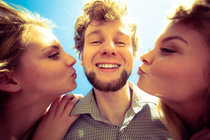 2 девушки целуя одного мальчика имея потеху внешнюю стоковое фото