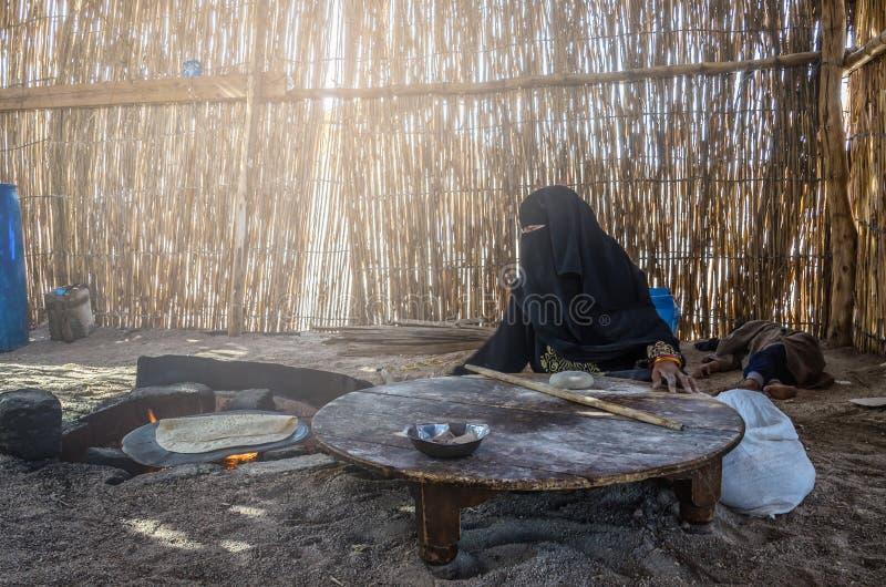 Египет, деревня бедуина, 28-ое августа 2017: Мусульманская женщина, сидя b стоковые фото