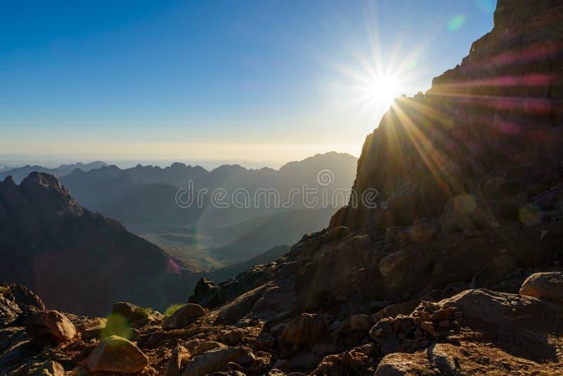 Египет, Синай, держатель Моисей Взгляд от дороги на которой паломники взбираются гора Моисея и рассвета - солнца утра с лучами на стоковое фото rf