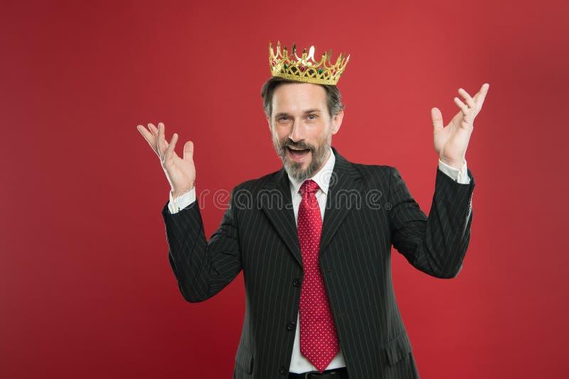 Его мечта быть чемпионом пришла истинный Увенчанный чемпион усмехаясь с кроной на красной предпосылке Счастливый наслаждаться биз стоковые фотографии rf