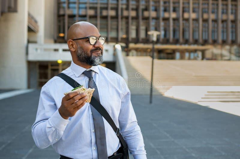 Еда бизнесмена принимает прочь сэндвич на открытом воздухе стоковое изображение rf