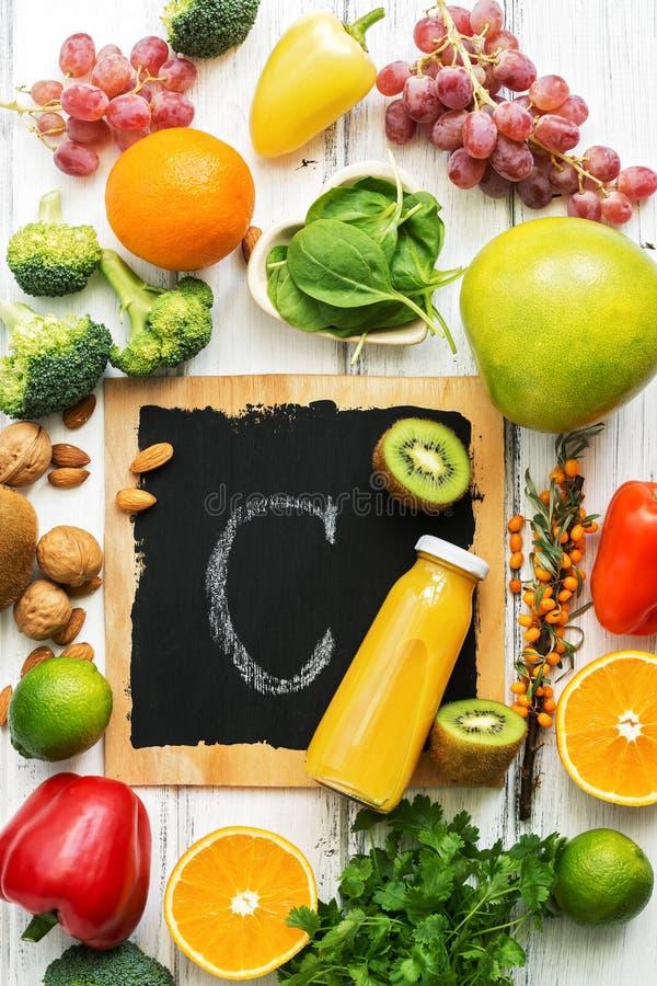 Еда высокая в витамин C Цитрус, брокколи, гайки, перец, виноградины, киви, крушина моря, шпинат Взгляд сверху, плоское положение стоковые фотографии rf