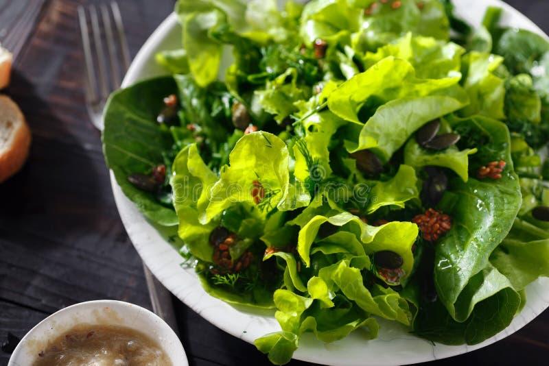 Еда диеты предпосылки семян льна зеленого салата плиты свежая темная деревянная стоковые изображения rf