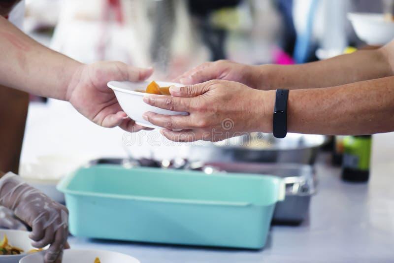 Еда доли волонтеров к бедным для того чтобы сбросить голод: Концепция призрения стоковая фотография rf
