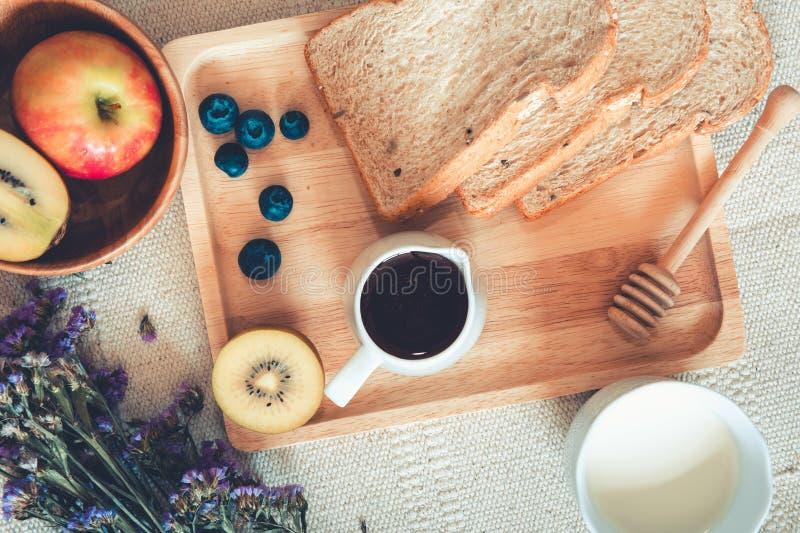 Еда домодельных и завтрака с горячим молоком, хлебом всей пшеницы, Яблоком, плодом кивиа голубики и медом на таблице , Еда питани стоковое изображение rf