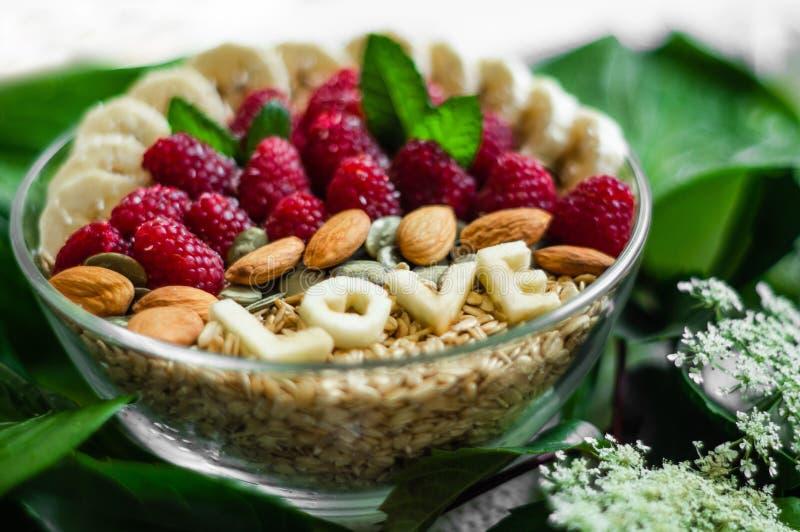 Еда здорового шара завтрака Слово ВЛЮБЛЕННОСТЬ в плите с здоровой едой Поленика, банан, гайки Вегетарианская принципиальная схема стоковые изображения