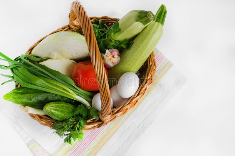 Еда и бакалеи в плетеной корзине для товаров на салфетке на белой предпосылке Корзина потребителя Магазин E Продажа стоковое фото