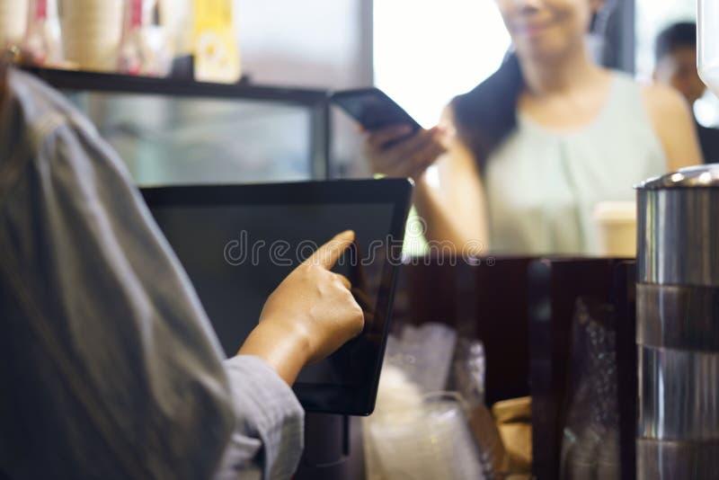 Еда и напиток заказа клиента, используя ее смартфон и высокую технологию nfs для того чтобы оплатить barista для ее приобретения  стоковая фотография rf
