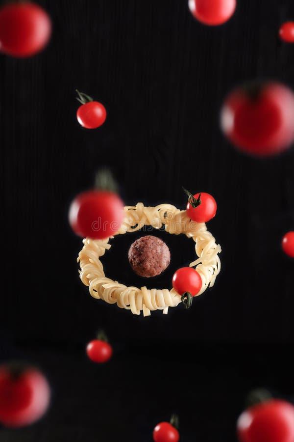 Еда летания Левитация fettuccine макаронных изделий с фрикаделькой и томатами Концепция фрикадельки как планета стоковые изображения