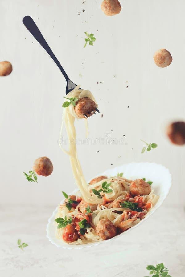 Еда летания Левитация fettuccine с фрикадельками, томатного соуса макаронных изделий, базилика на белой предпосылке стоковое фото