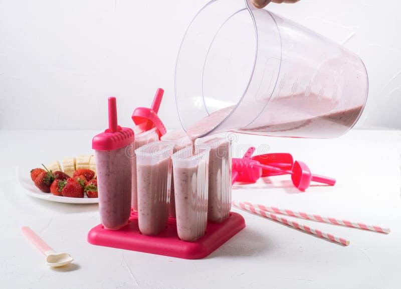 Еда лета: варить самодельный лед плодоовощ Заполнять подготовленную массу в прессформах мороженого стоковое изображение rf