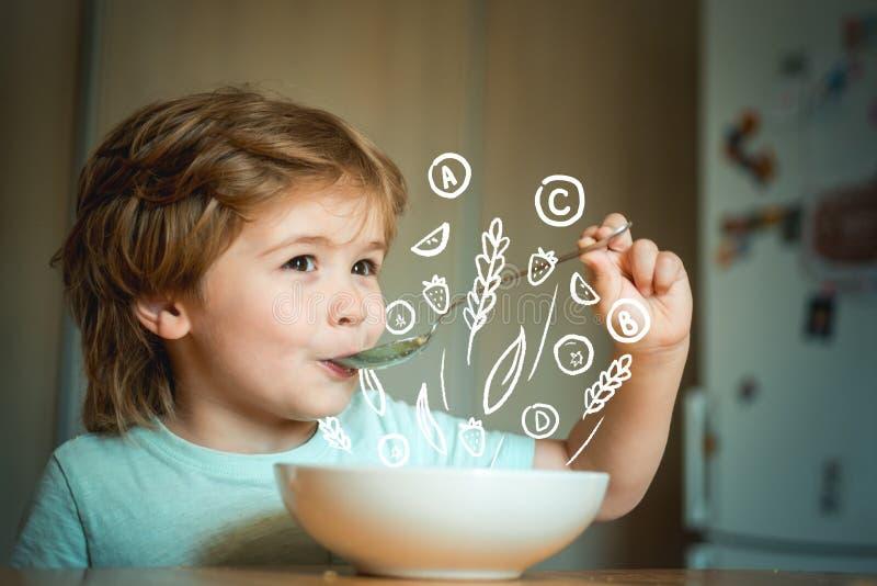 Еда ребенк Мальчик имея завтрак в кухне Родительство r Молодой парень сидя на еде таблицы стоковая фотография
