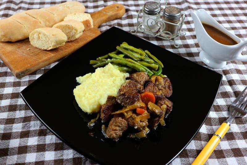 Еда с овощами говядины поломала зеленый цвет картошек, который будут едой стоковая фотография