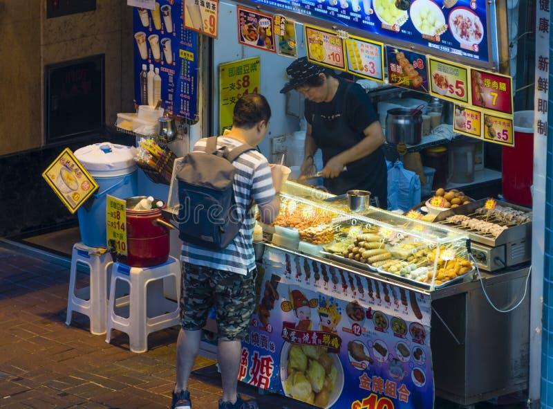 Еда улицы людей покупая на стойле еды в Гонконге стоковые фотографии rf