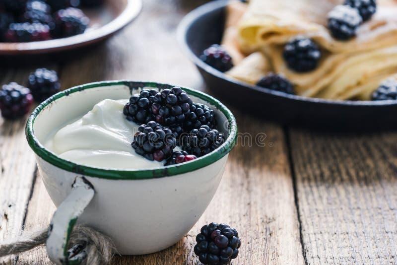 Еда утра, йогурт, свежие ежевики лета в сельской кружке стоковая фотография