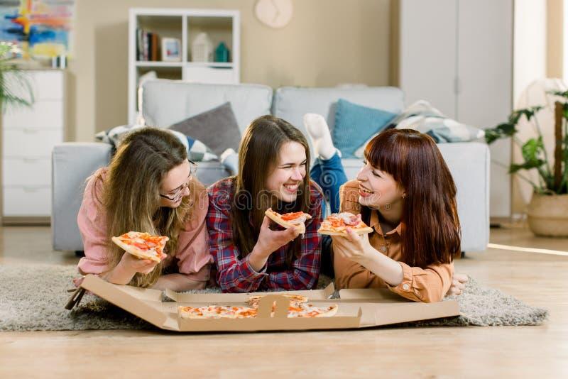 Еда фаст-фуда Счастливые 3 красивых друз смеясь, ел партию пиццы дома Женщины имея обедающий совместно стоковая фотография
