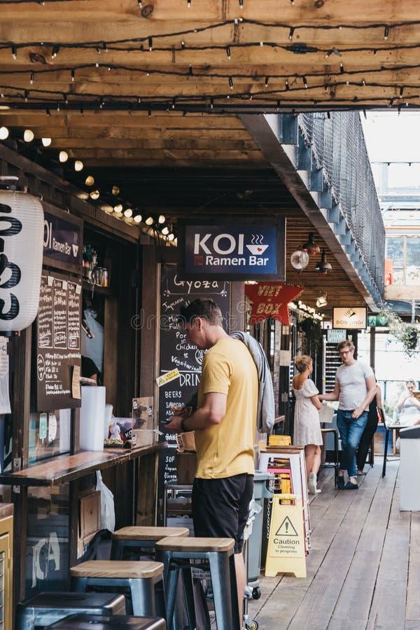 Еда человека приказывая от рамэнов KOI в попе Brixton, Лондоне, Великобритании стоковые изображения