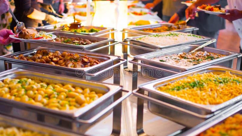 Еда шведского стола ресторанного обслуживании группы людей крытая в роскошном ресторане стоковые фотографии rf