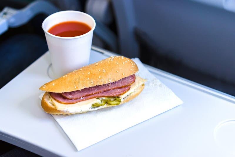 Еда эконом-класса летная, сандвич и сок томата на складном столике стоковая фотография