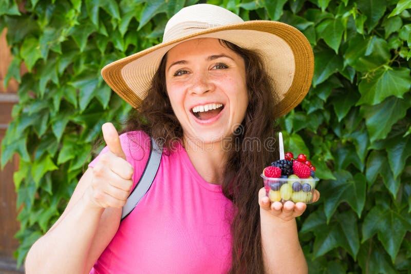 Еда Eco и здоровая концепция образа жизни - портрет усмехаясь женщины держа ягоды и показывая большой палец руки вверх показывать стоковая фотография rf