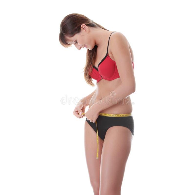 ее измеряя детеныши женщины шкафута стоковое фото