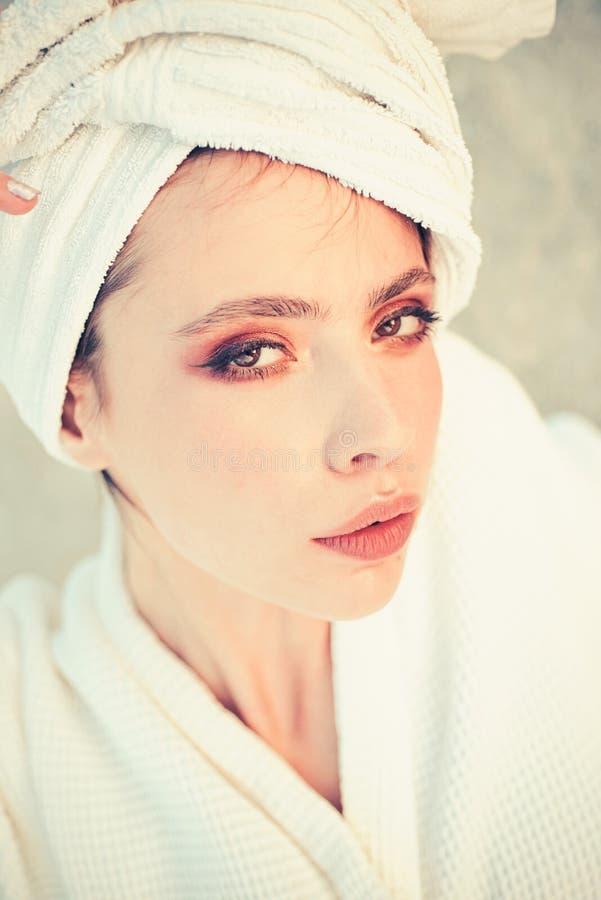 Ее режим haircare Режим красоты и забота гигиены Милое полотенце ванны носки женщины на голове Молодая женщина в купать мантию стоковое изображение