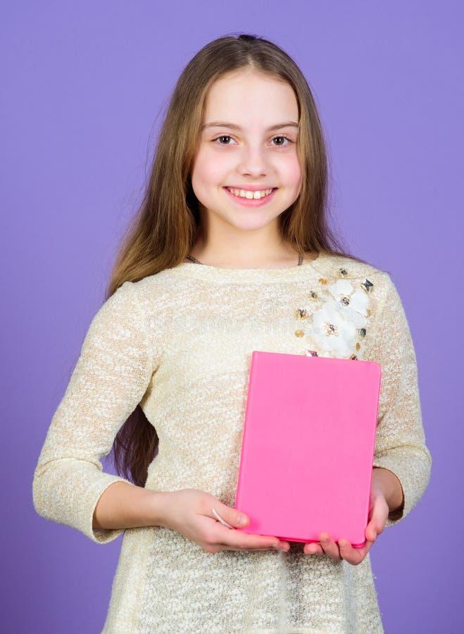 Ее хобби читает Милая небольшая книга удерживания ребенка для домашнего чтения Прелестная маленькая девочка наслаждается книгами  стоковое фото