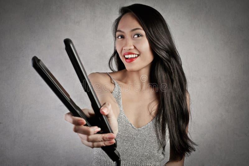 Ее любимое straitener волос стоковая фотография