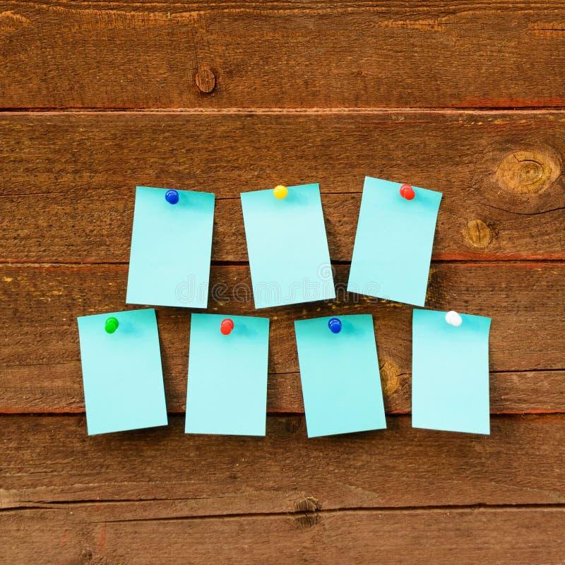 Еженедельный план-график с голубой бумагой 7 над деревянной предпосылкой стоковое изображение