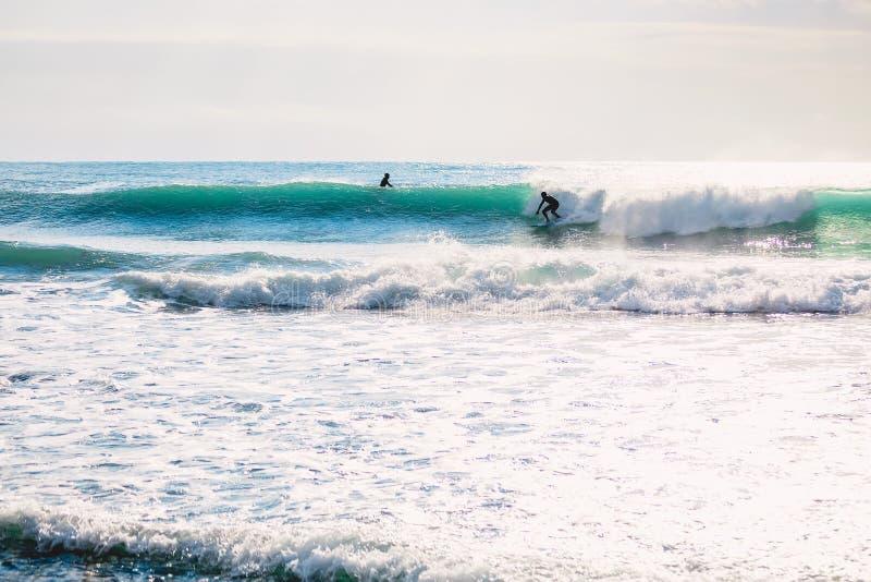 Езда серфера на идеальной голубой волне Зима занимаясь серфингом в океане стоковое фото rf