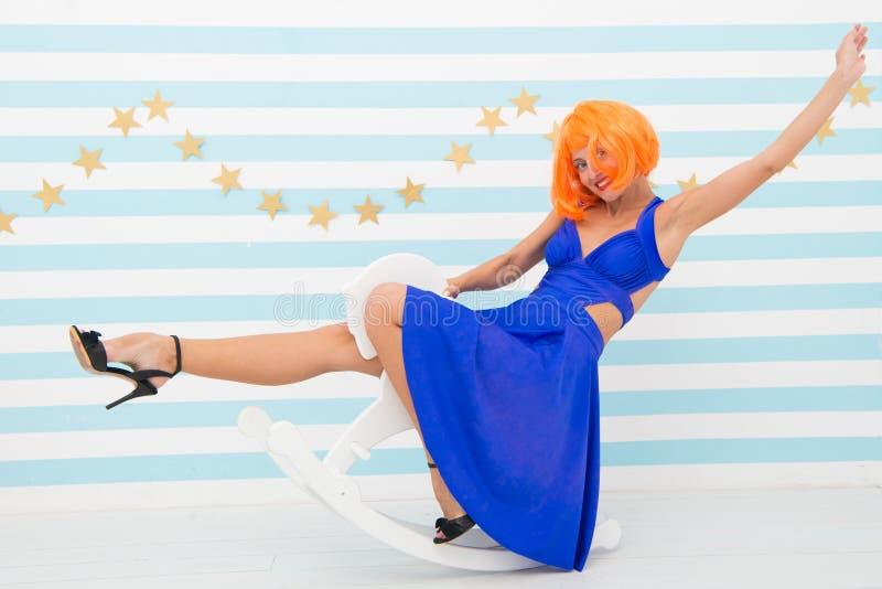 Езды парика девушки отбрасывают маленькую лошадь Чувство ребяческое Красный цвет дамы или платье парика имбиря голубое едут тряся стоковые изображения rf