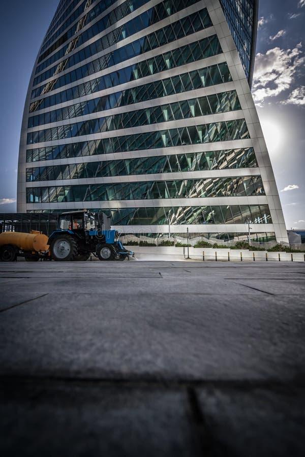 Езды трактора на дороге против небоскреба стоковые изображения rf