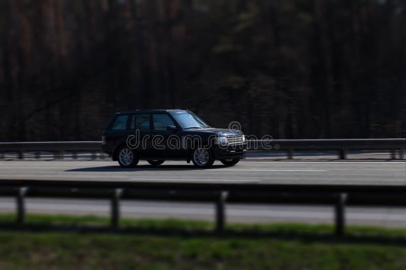 Езды черноты Range Rover на дороге Против предпосылки запачканных деревьев стоковое фото rf