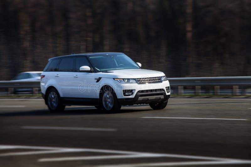 Езды Range Rover Land Rover белые на дороге Против предпосылки запачканных деревьев стоковые фото